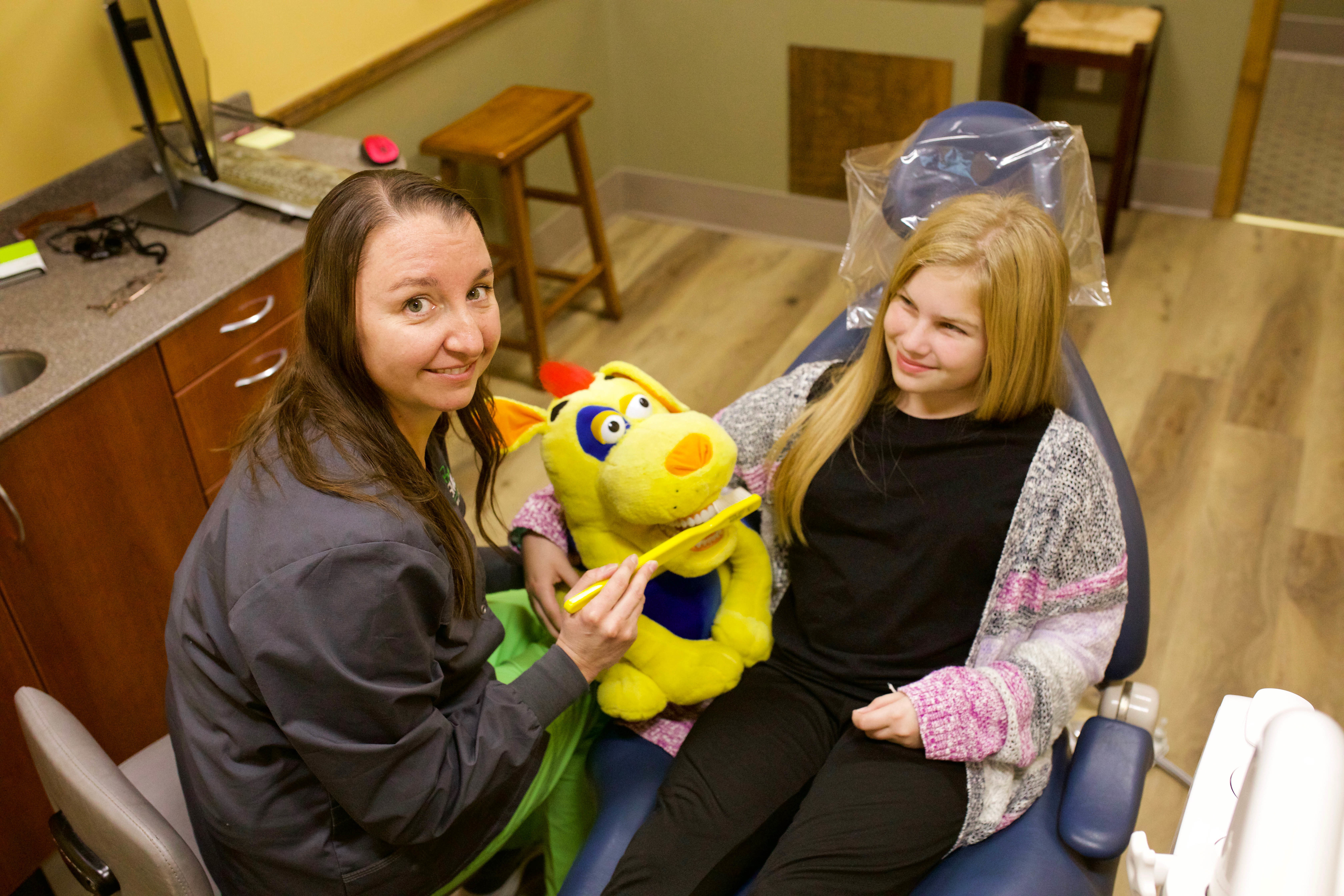 Carrie showing a patient how to brush using the Dog puppet.
